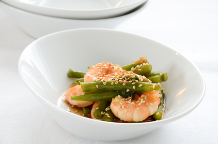 greeen: Shrimps and green beans salad with sesame in a white bowl