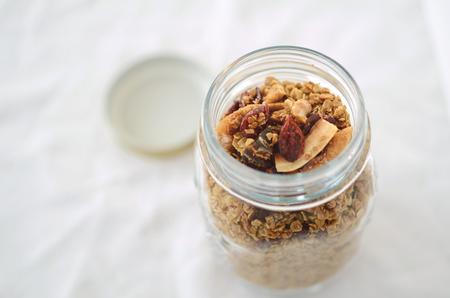 frutos secos: granola casera con frutos secos y coco rallado en un tarro de cristal Foto de archivo