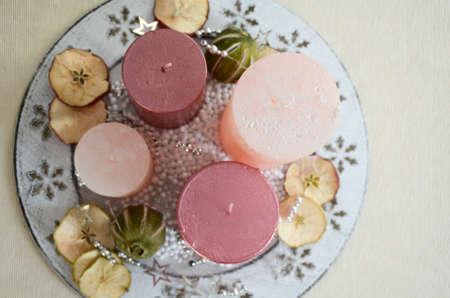 frutos secos: decoración de la mesa de Navidad en tradtion europeo con cuatro velas de color rosa y frutos secos esparcidos en la vista desde arriba la placa blanca