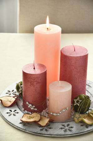 german swiss: Christmas table decoration in european tradtion with four pink candles and dried fruits scattered on the white plate Stock Photo