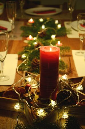 subdued: Christmas table decoration with red candle and fir tree twigs lying on the table with electric garland lights on