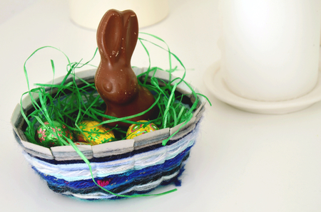 crafty: Handmade easter basket with a chocolate bunny and eggs on white background