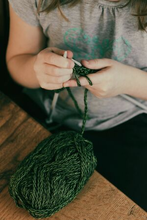Girl sitting at the table and knitting with green yarn closeup