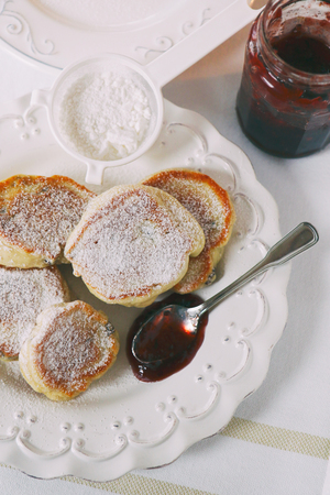 caster: Thick pancakes on white plate with jam and caster sugar Stock Photo