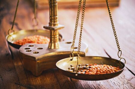 Vintage balance scales with two pans and masses weighing red lentil