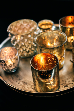 Sparkling candle cups with tealight candles burning golden on a tray Stock Photo