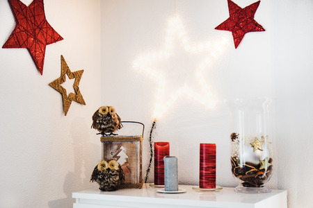 Christmas interior decoration on the wall and sideboard with owls and red stars Stock Photo