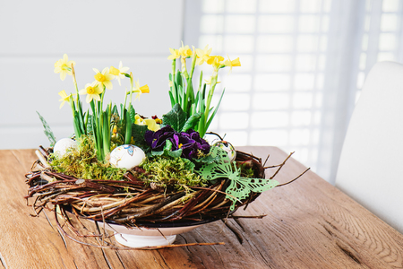 Easter table centerpiece decoration with daffodils and easter eggs arranged in a rustic wreath made of tree twigs