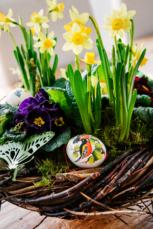 Easter table centerpiece decoration with daffodils and easter eggs arranged in a rustic wreath made of tree twigs. Close-up with details.
