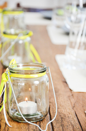 Glass jar with tea candles inside. Table decoration in yellow and green colours for dinner in spring or summer.