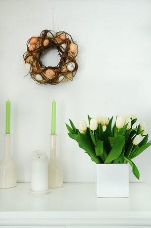 White tulips on sideboard wih easter egg wreath hanging on white wall