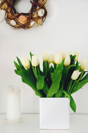 White tulips on sideboard wih easter egg wreath hanging on white wall, closeup. Stock Photo