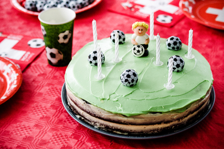 Kids birthday party Football theme. Chocolate cake decorated like football field with seven candles.