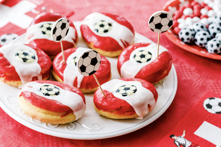 Doughnuts and chocolate candy im football theme on red table cloth. Football party at home with snacks and sweets. Football fever worldwide. Stock Photo