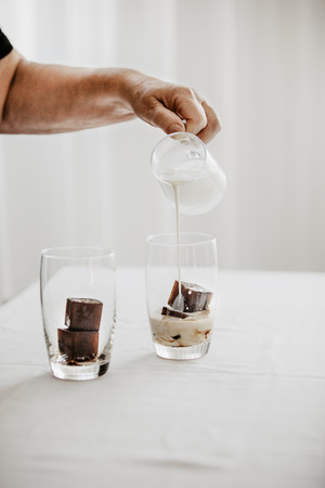 Woman preparing iced coffee. Frozen coffee ice cubes in a glass poured with milk to make a refreshing summer drink. White background. Body parts.