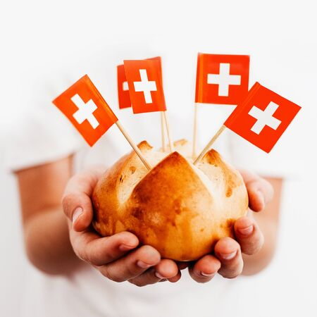 Traditional swiss bread buns called in German 1.Augustweggen baked in Switzerland to celebrate Swiss National Day on August 1st. Body parts, children hands holding bread. Swiss flags on wooden toothpicks. White background, isolated, copy space.