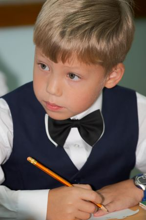 Young boy thinking about lesson in classroom Stock Photo - 2305443