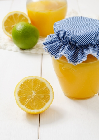 A jar of lemon curd with the lemon and lime on the white table photo