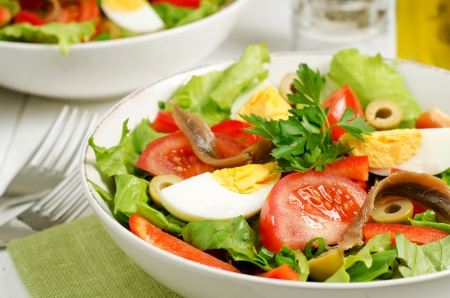 Salad Nicoise with tomatoes, green beans, tuna, eggs and anchovies dressed with vinaigrette photo