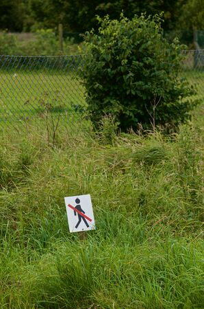 ideogram: pictogram sign in grass area. Daylight cloudy. Stock Photo