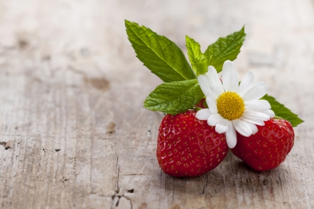 Strawberries on wooden background with daisy Stock Photo