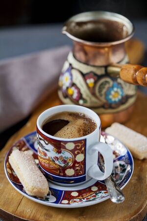 Coffee in a cup with cezve on the background  Stock Photo