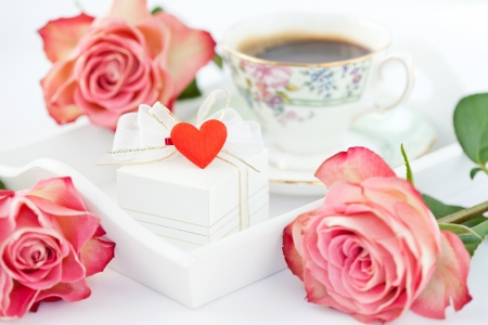 Romantic setup with roses, gift box and coffee
