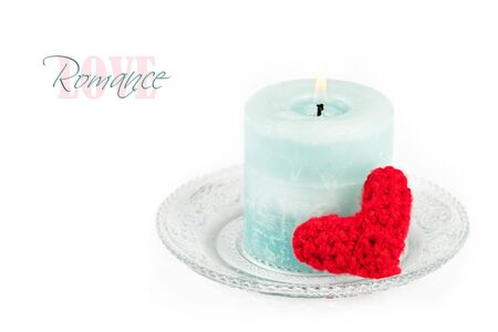 Blue candle and hand knitted heart on white photo