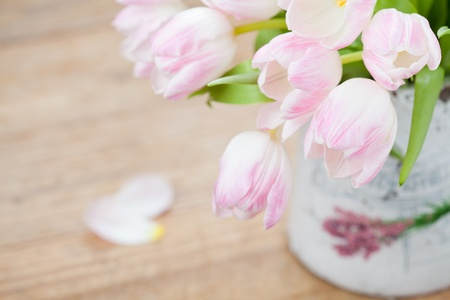 Pink tulips in vase on wooden background