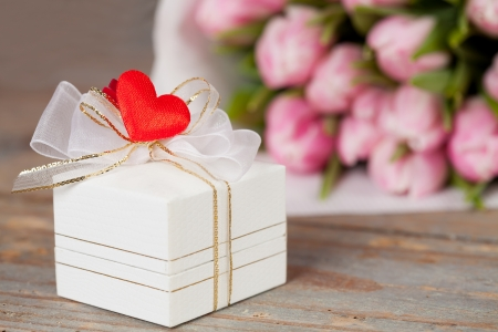 Gift box with pink tulips on the background