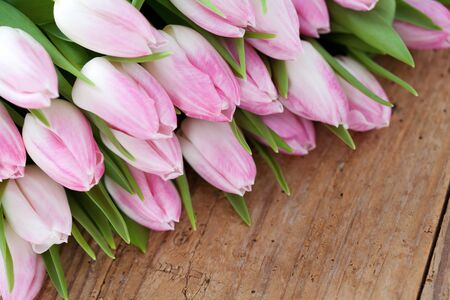 Bunch of beautiful pink tulips on wooden background Stock Photo