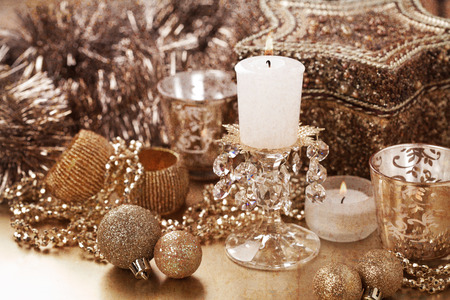 Christmas composition with decorations and candles in golden colour