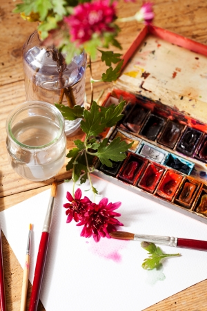 Watercolor paint box, flowers and brushes for painting