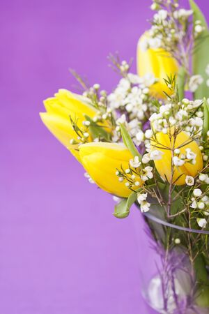 Bouquet of yellow tulips in vase on purple background, selective focus