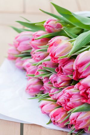 Bunch of beautiful pink tulips on wooden table Stock Photo