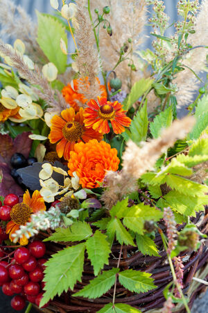 Bouquet of autumn flowers and berries in basket