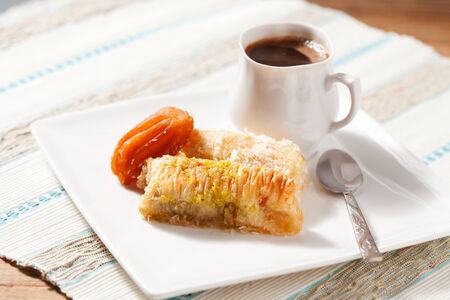 Oriental sweets assortment with cup of coffee, textured