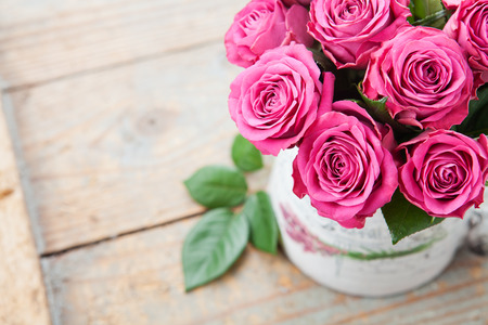 Bouquet of beautiful pink roses on wooden