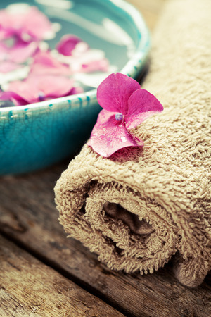 Bottle of essential oil, bowl with flowers and towel. Spa concept