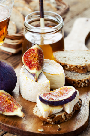 Breakfast setting with bread, cheese, figs and honey Stock Photo