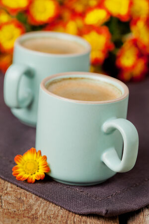 Cup of cofee with bright autumn flowers