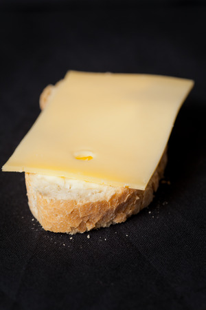 Buttered piece of artisan wheat bread with slice of cheese Stock Photo