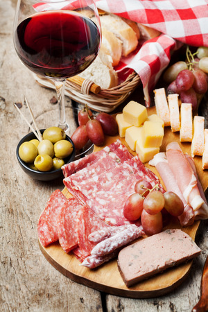 Glass of red wine with charcuterie assortment on the background 免版税图像