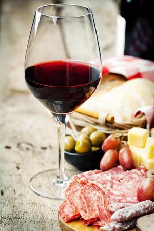 salami: Copa de vino tinto con el surtido de embutidos en el fondo