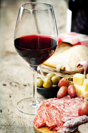 antipasto: Glass of red wine with charcuterie assortment on the background Stock Photo