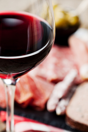 Glass of red wine with charcuterie assortment on the background photo