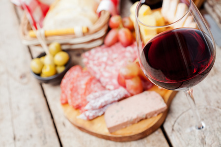 Glass of red wine with charcuterie assortment on the background 스톡 콘텐츠