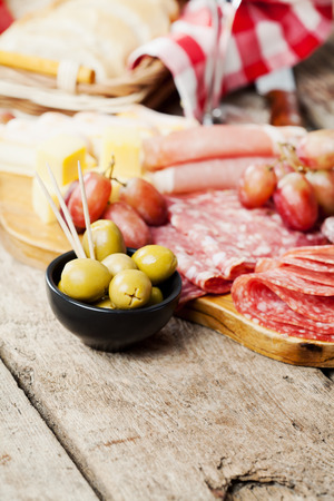 Charcuterie assortment and olives on wooden background photo