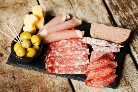 meat dish: Charcuterie assortment and olives on wooden background