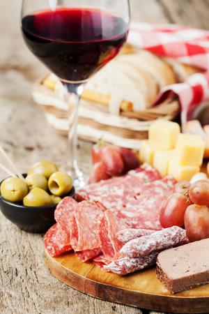 charcutería: Copa de vino tinto con el surtido de embutidos en el fondo